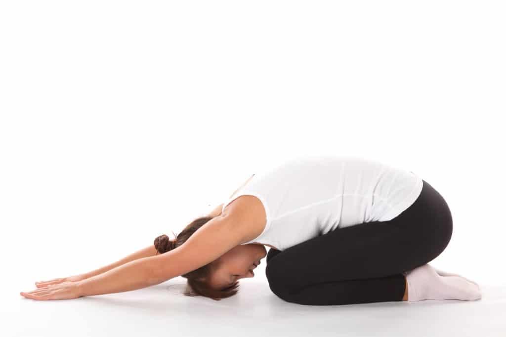 žena, která cvičí jógu na podložce