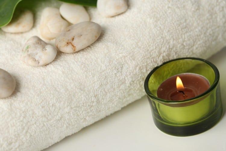 wellness zátiší - hořící svíčka a složený ručník