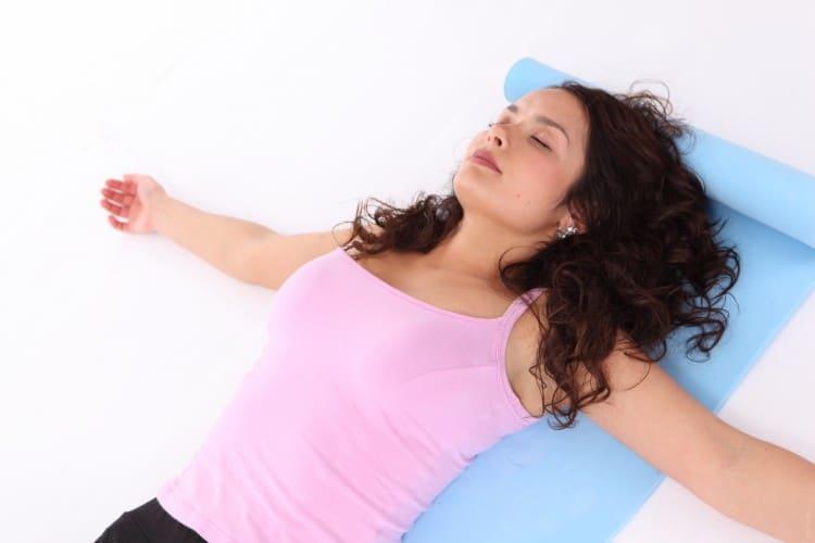 žena v růžovém tílku ležítí na modré jóga podložce