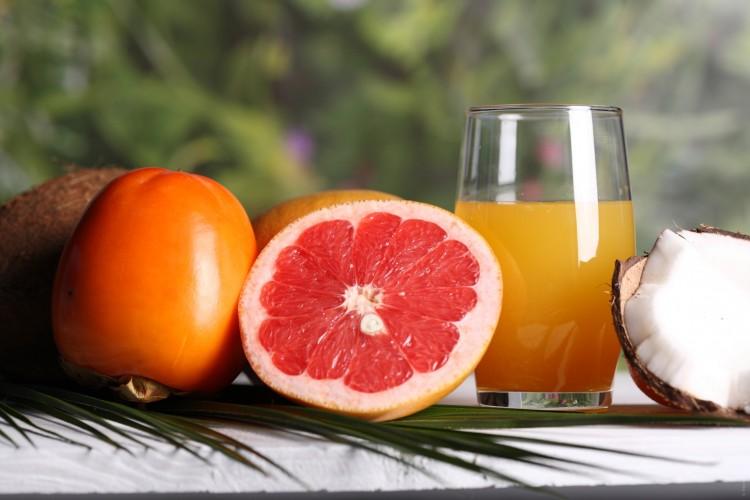 Pomeranč, grep, kokos a ovocný džus na stole