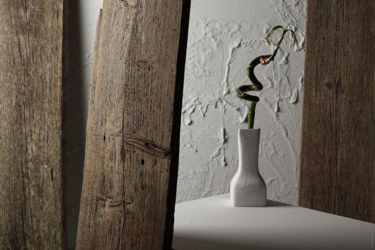 designová bílá váza s bambusem na stole