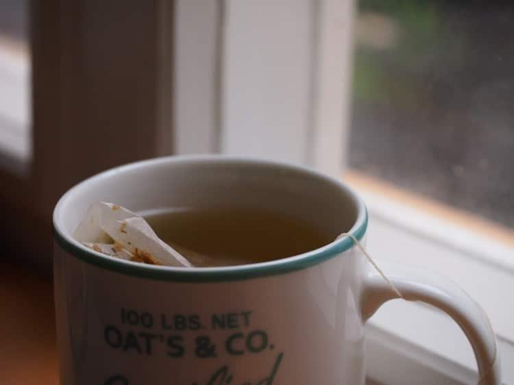 zelený sáčkový čaj v bílém hrníčku