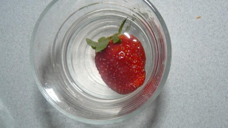 sklenice vody s čerstvou jahodou