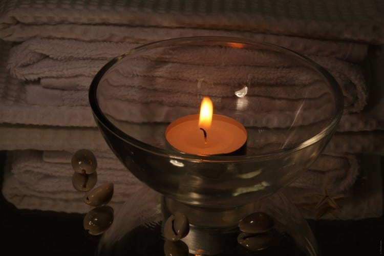 Wellnes zátiší s čajovou svíčkou ve skle, skleněnými kuličkami a ručníky