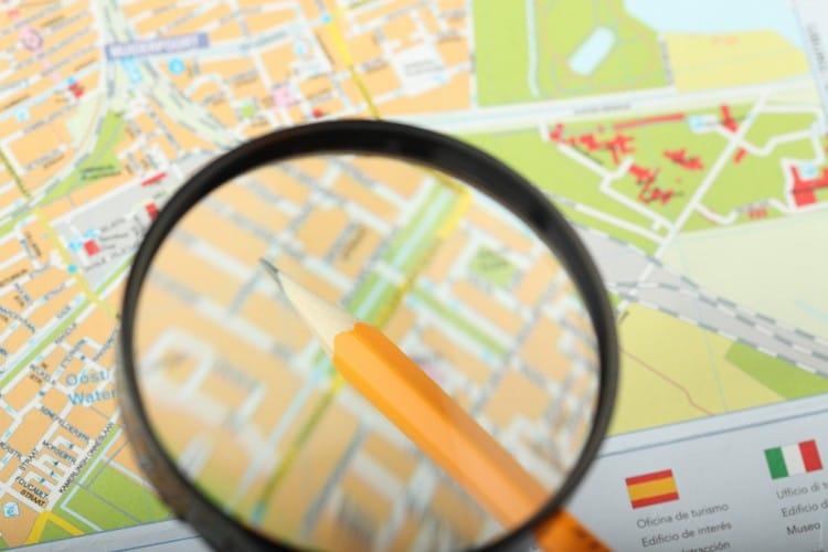 Fotka mapy, nad kterou je tužka zvětšená lupou