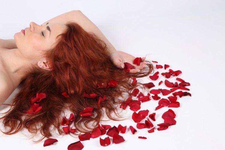 Žena relaxující na plátích růží
