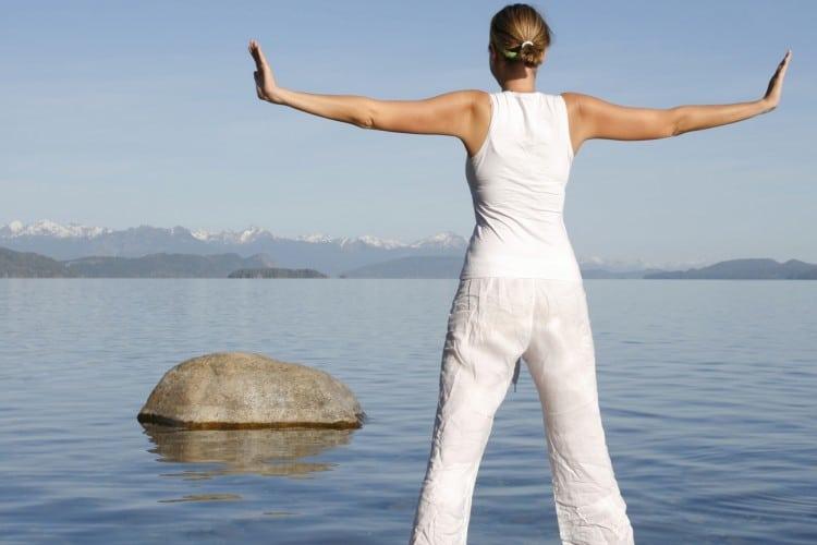 Žena v bílém oblečení medituje na břehu jezera