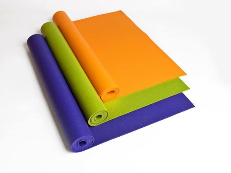 Tři barevné dětské podlžky na jógu na bílém pozadí