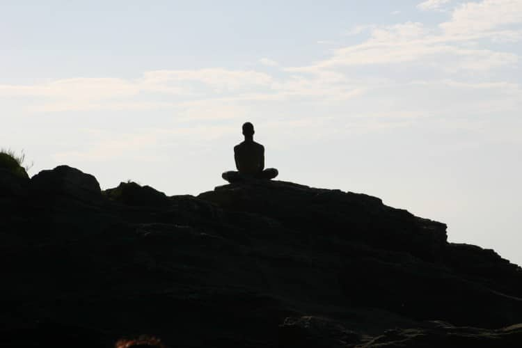 Muž sedící v tureckém sedu na vrcholku hory