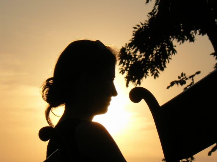 Žena z profilu v pozadí se západem slunce