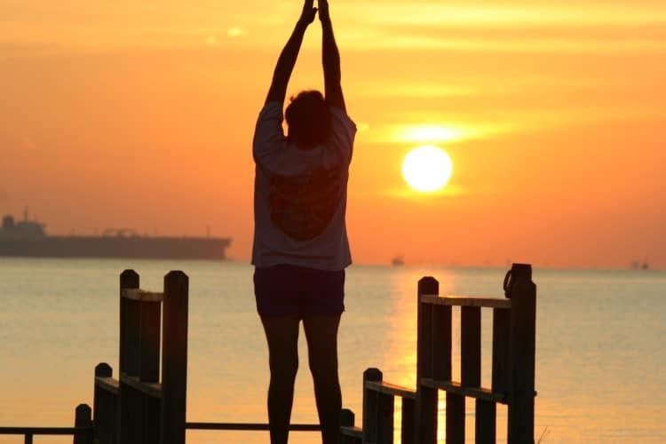 Člověk cvičící jógu při východu slunce na mořském molu
