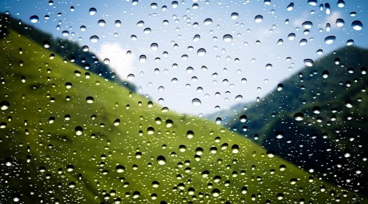 fotka venkovní krajiny s deštěm přes okno