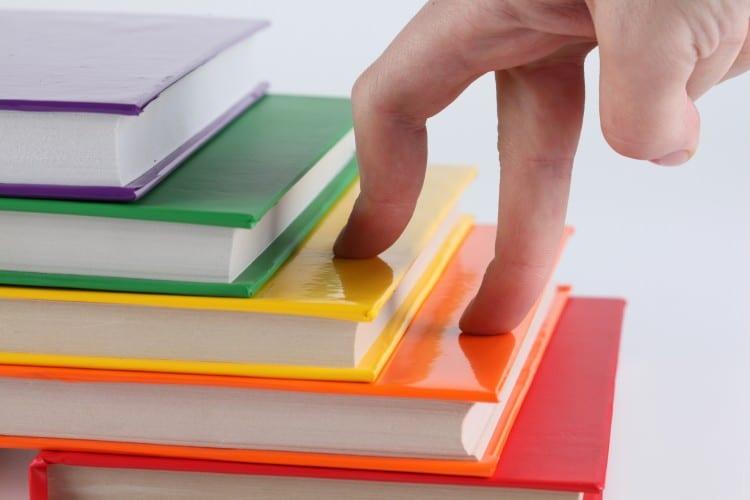 fotka lidských prstů, které jsou po schodech z knih