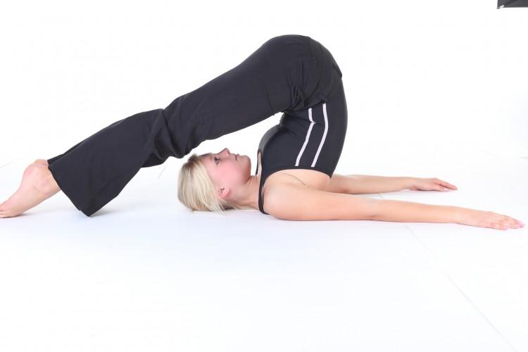 žena cvičící jógy v černém cvičebním oblečení