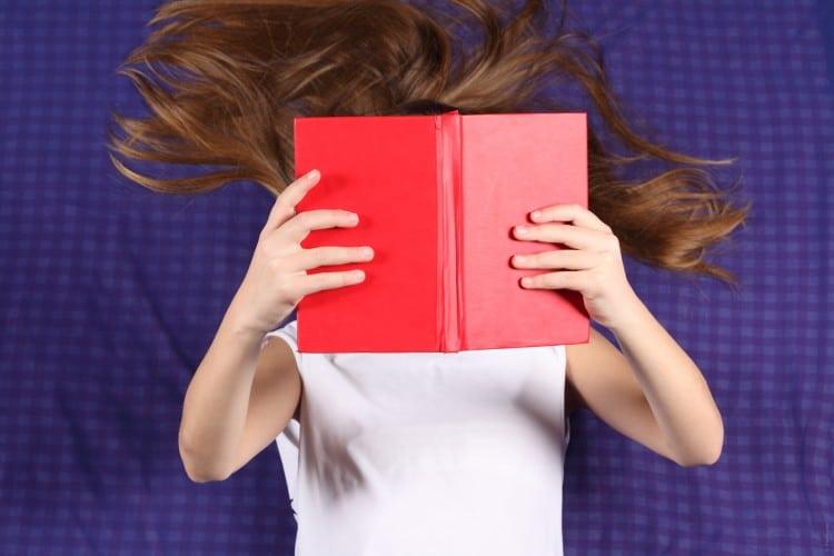 Dívka si čte v leže červenou knížku