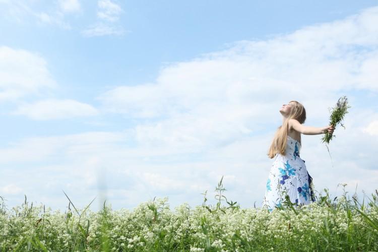 mladá žena se raduje ze slunce na louce