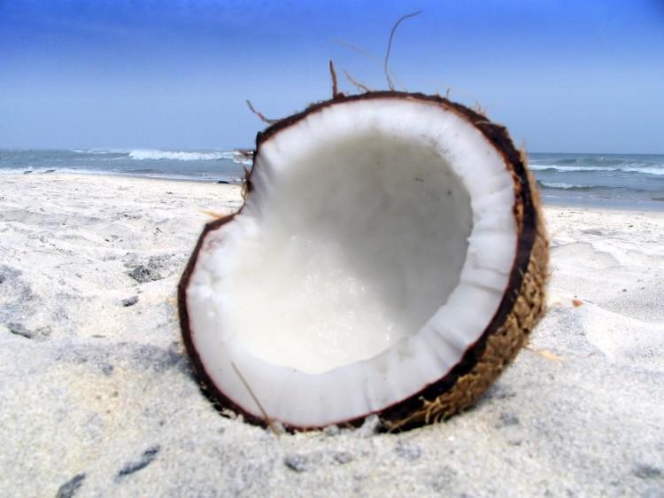 Fotka rozpůleného kokosu na pláži