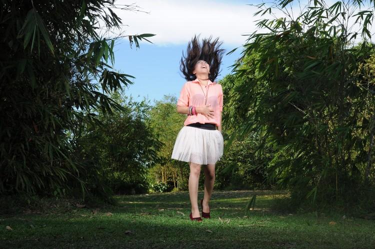 Dívka v parku vyfocená při výskoku do vzduchu