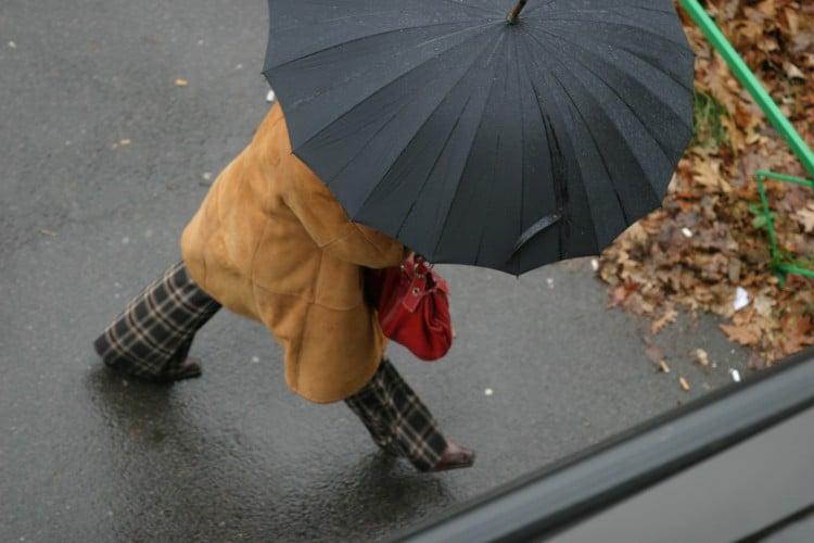 Žena s černým deštníkem jde po ulici