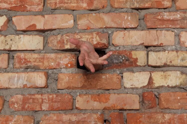 Lidská ruka vykukuje z cihlové zdi
