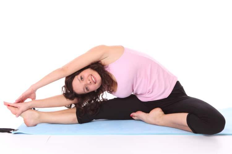 Žena cvičící jógu na modré podložce v růžovém tílku