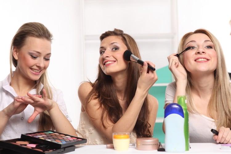 Tři mladé ženy se líčí před zrcadlem