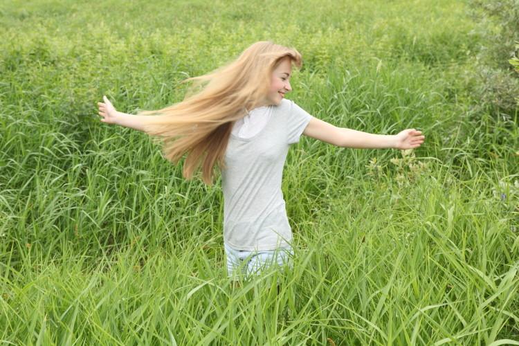 Mladá dívka s dlouhými vlasy běhá po louce