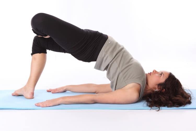 Hnědovlasá dívka cvičí jógu na modré podložce