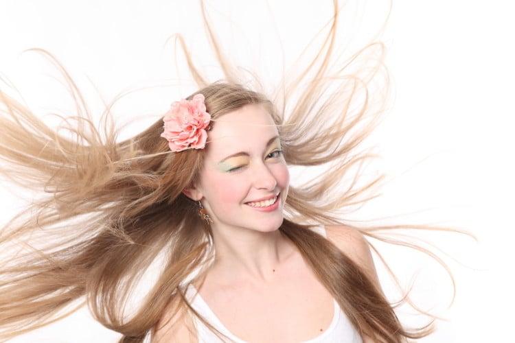 Žena s blond vlasy, které jsou rozevláté do stran