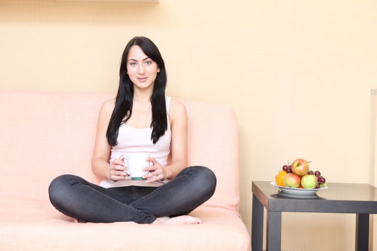 Žena sedí v bílém tílku na gauči a drží hrníček s čajem