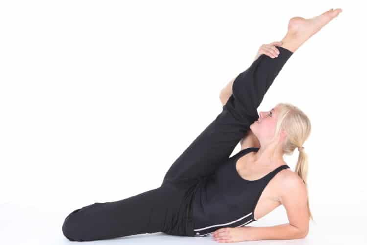 Žena, která cvičí jógu v černém sportovním oblečení