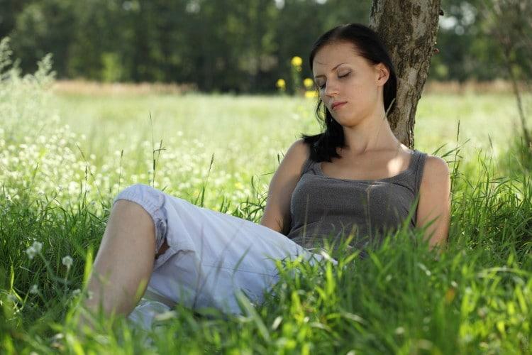 Žena, které odpočívá na louce v tříčtvrtečních kalhotech