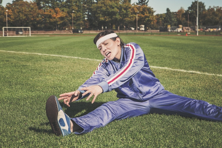 Žena, která se protahuje na trávníku ve sportovním oblečení