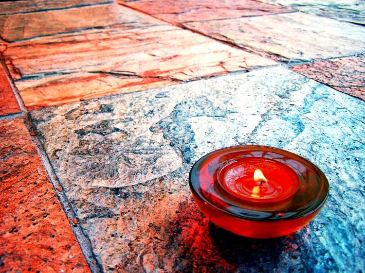 Červená svíčka v podstavci postavená na podlaze