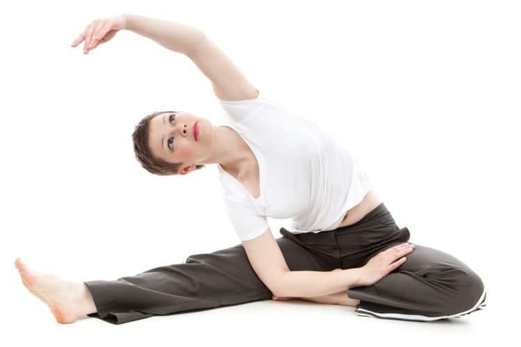 Žena s krátkými vlasy cvičí jógu v bílém tričku