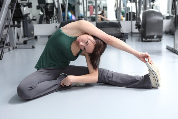 Žena se protahuje ve sportovním oblečení na zemi ve fitnesscentru