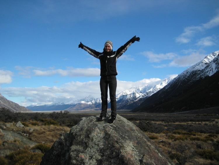 Žena stojí v zimní krajině na balvanu a roztahuje ruce