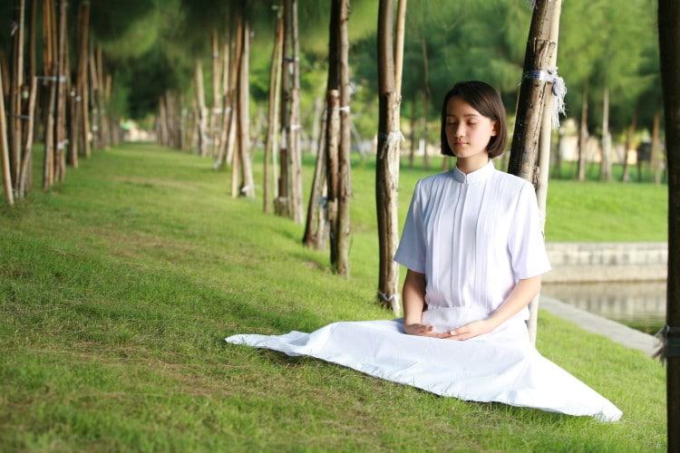 Žena v bílém oblečení, která medituje v přírodě