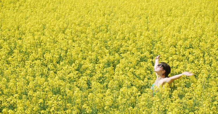 Žena stojí v rozkvetlém řepkovém poli