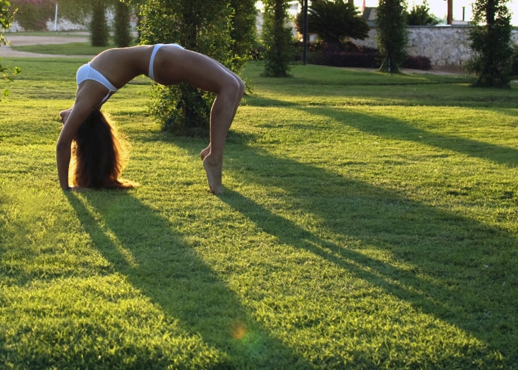 Žena v bílých plavkách cvičí jógu na zahradě