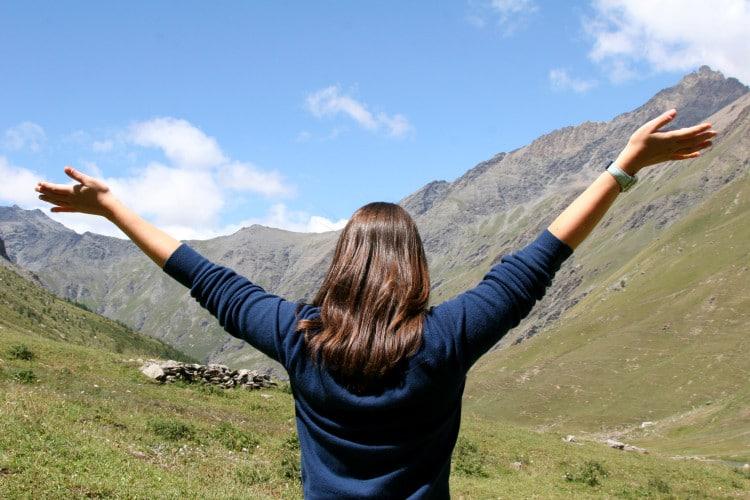 Žena stojí v přírodě s rozpaženýma rukama