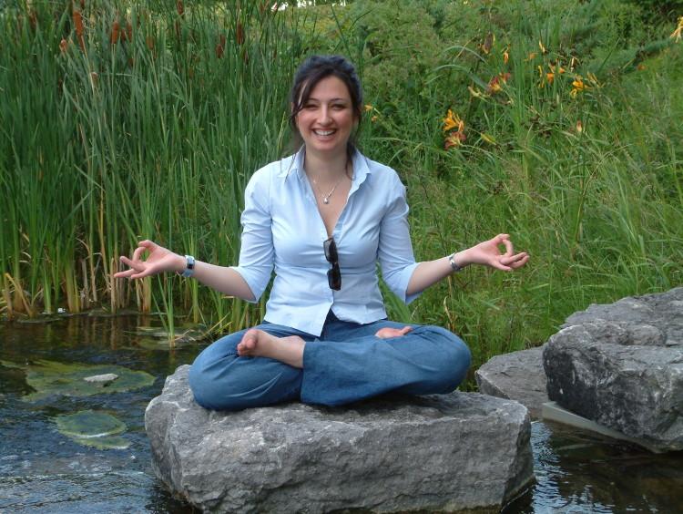 Žena cvičí jógu na kamenu v potoce