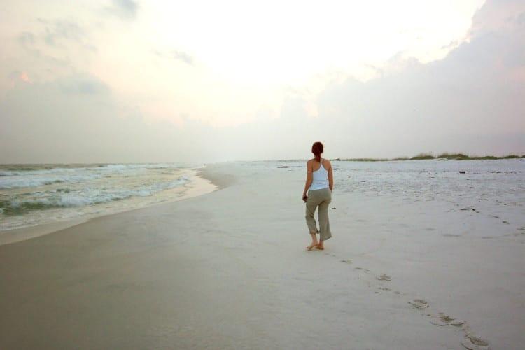 Mladá žena se prochází po liduprázdné pláži