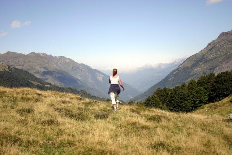 Žena jde na procházce po horách