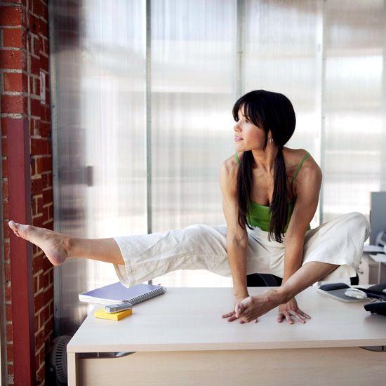 Žena cvičí jógu na pracovním stole v práce
