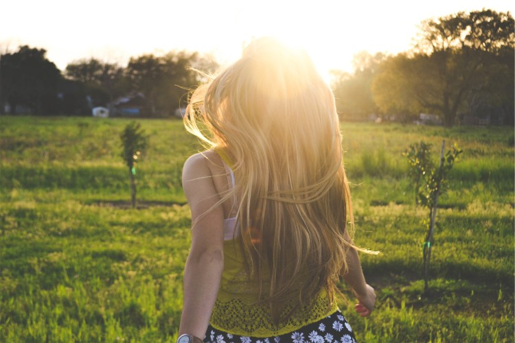 Dívka s dlouhými vlasy běží na louce