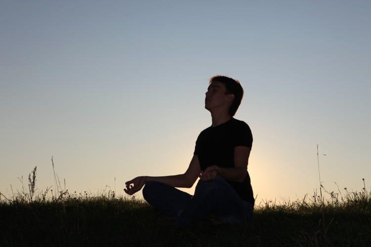 Muž meditující na trávě