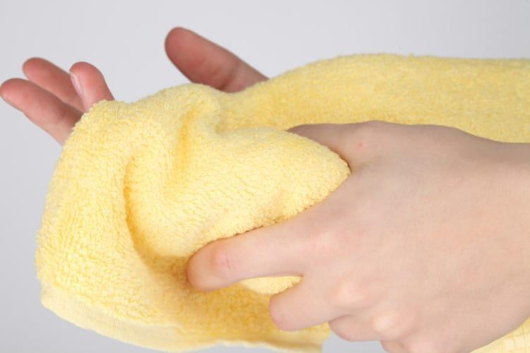 Žena si utírá ruce žlutým ručníkem