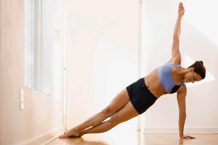 Žena cvičí pozici bočního prkna