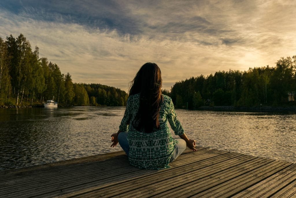 Žena sedící na mole v lotusovém sedě